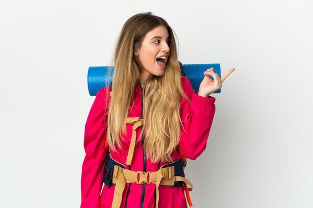Jeune alpiniste femme avec un gros sac à dos sur un mur isolé dans l'intention de réaliser la solution tout en soulevant un doigt