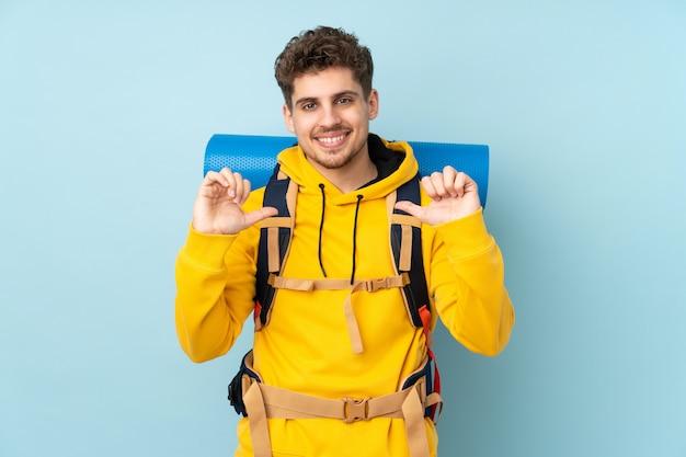 Jeune alpiniste avec un gros sac à dos isolé sur le mur bleu fier et satisfait de lui-même