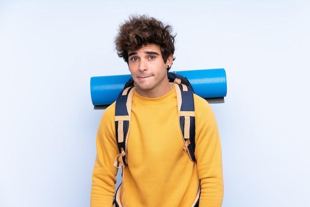 Jeune alpiniste avec un gros sac à dos sur un mur bleu isolé ayant des doutes et avec une expression de visage confuse