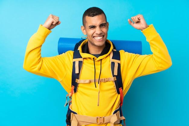 Jeune alpiniste avec un gros sac à dos sur le mur bleu isolé célébrant une victoire