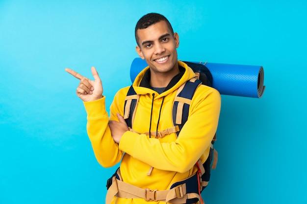 Jeune alpiniste avec un gros sac à dos sur le mur bleu isolé pointant le doigt sur le côté