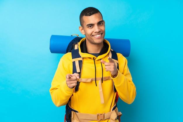 Jeune alpiniste avec un gros sac à dos sur le mur bleu isolé pointe du doigt sur vous