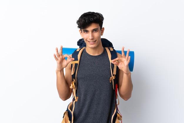 Jeune alpiniste avec un gros sac à dos sur un mur isolé