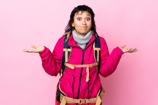 Jeune alpiniste avec un gros sac à dos sur le mur rose ayant des doutes avec l'expression du visage confus