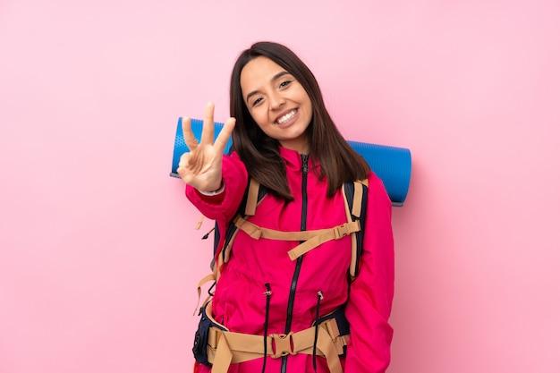 Jeune alpiniste avec un gros sac à dos sur un mur rose isolé heureux et en comptant trois avec les doigts