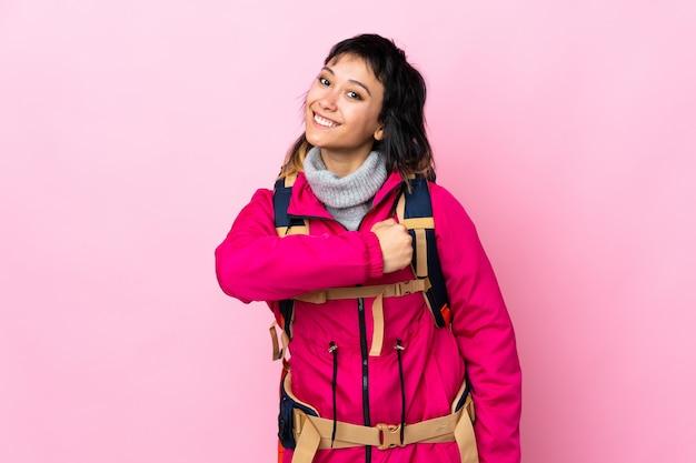 Jeune alpiniste avec un gros sac à dos sur rose isolé célébrant une victoire