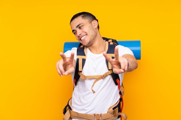 Jeune alpiniste homme asiatique avec un gros sac à dos isolé sur mur jaune souriant et montrant le signe de la victoire