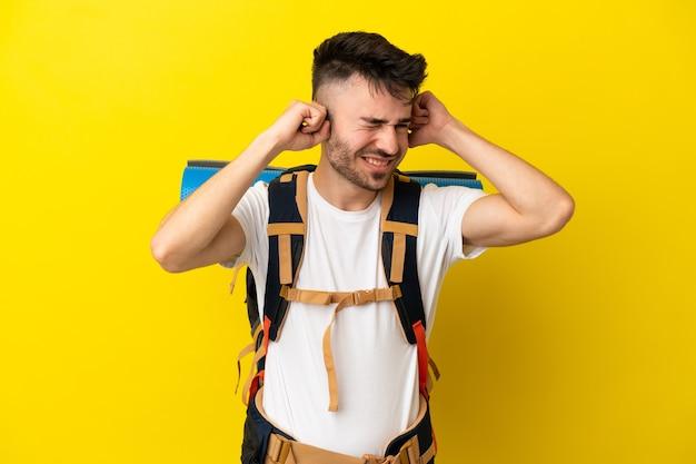 Jeune alpiniste homme caucasien avec un gros sac à dos isolé sur fond jaune frustré et couvrant les oreilles