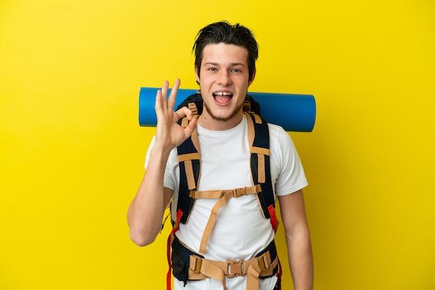 Jeune alpiniste homme russe avec un gros sac à dos isolé sur fond jaune montrant un signe ok avec les doigts