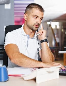 Un jeune et ambitieux trader boursier conclut une affaire par téléphone dans un bureau occupé rempli d'ordinateurs.