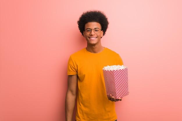 Jeune, américain africain, tenue, a, pop-corn, seau, gai, à, a, grand sourire