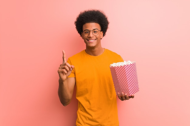 Jeune, américain africain, tenue, a, pop-corn, seau, projection, numéro un