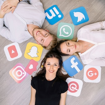 Jeune ami heureux couché sur le sol avec les logos de médias sociaux