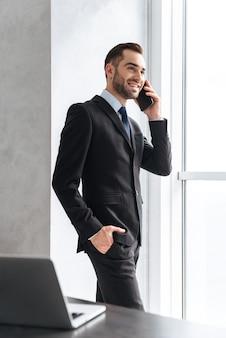 Jeune amn confiant portant un costume debout à l'intérieur à la fenêtre, utilisant un téléphone portable