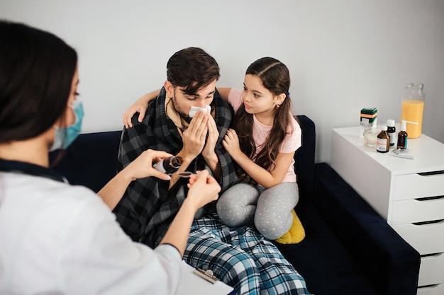 Jeune amn malade assis sur un canapé et éternuant. sa fille assise à côté. elle le réconforte. femme médecin versant du sirop dans une cuillère.