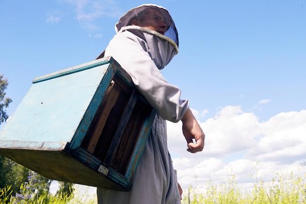 Jeune apiculteur contre le ciel bleu