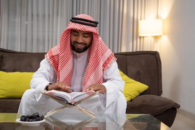 Un jeune arabe souriant en lisant le coran