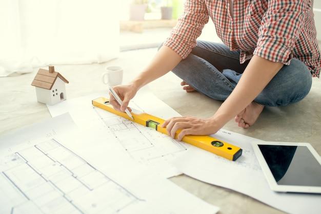 Jeune architecte asiatique beau mâle travaillant à la maison sur le sol.