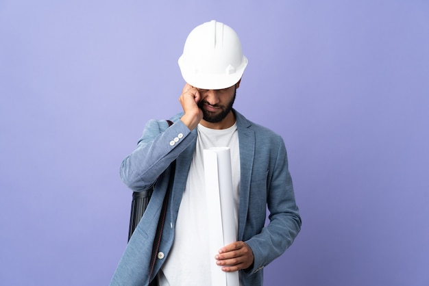Jeune architecte avec casque parlant au téléphone et tenant des plans