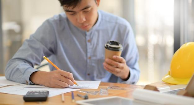 Un jeune architecte est en train de rédiger un design de maison et tient une tasse de café dans un bureau moderne.
