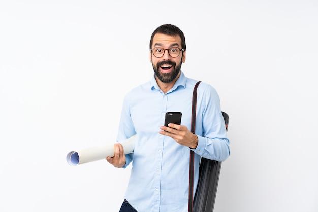 Jeune architecte homme à la barbe sur blanc isolé surpris et envoyant un message