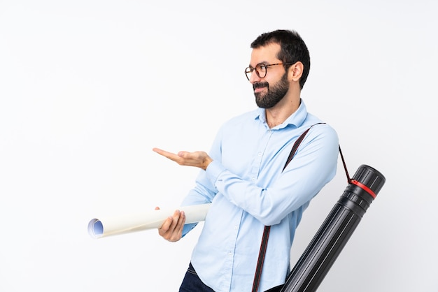Jeune architecte homme à la barbe sur mur blanc isolé, étendant les mains sur le côté pour inviter à venir