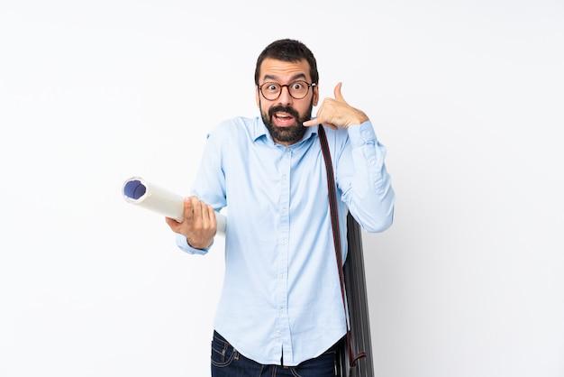Jeune architecte homme à la barbe sur mur blanc isolé, faisant un geste de téléphone et doutant