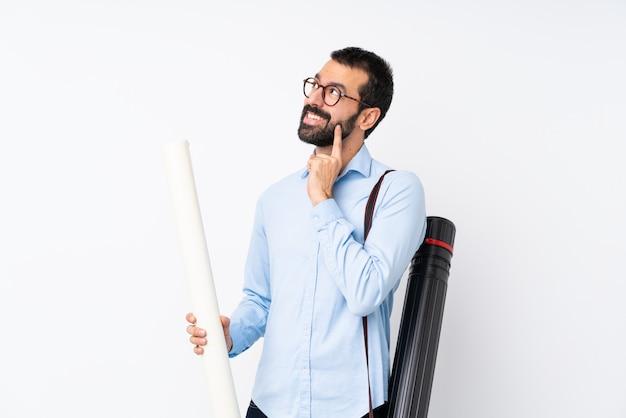Jeune architecte homme à la barbe sur mur blanc isolé, pensant à une idée tout en levant