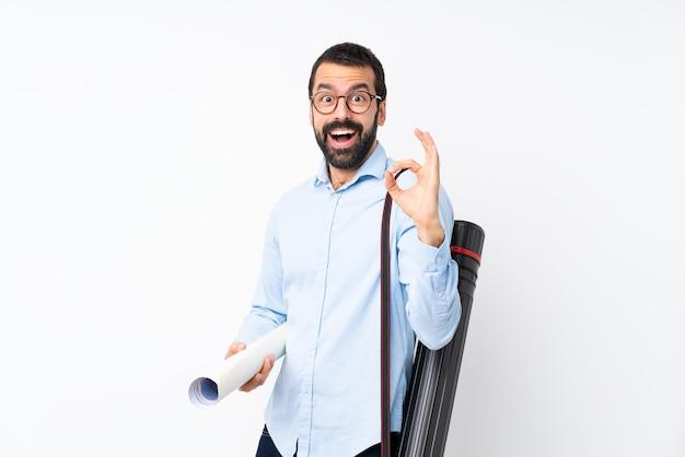 Jeune architecte homme à la barbe sur un mur blanc isolé surpris et montrant un signe ok