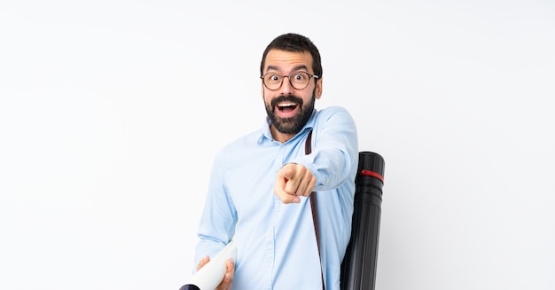 Jeune architecte homme à la barbe sur un mur blanc isolé surpris et pointant le devant