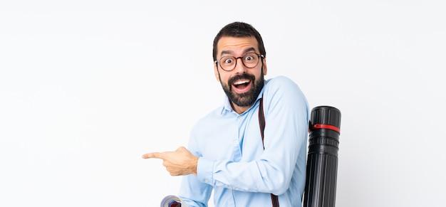 Jeune architecte homme à la barbe sur mur blanc isolé surpris et pointant le doigt sur le côté