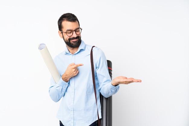 Jeune architecte homme à la barbe sur mur blanc isolé tenant une surface imaginaire sur la paume pour insérer une annonce