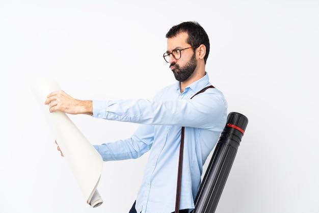 Jeune architecte homme à la barbe sur mur blanc isolé