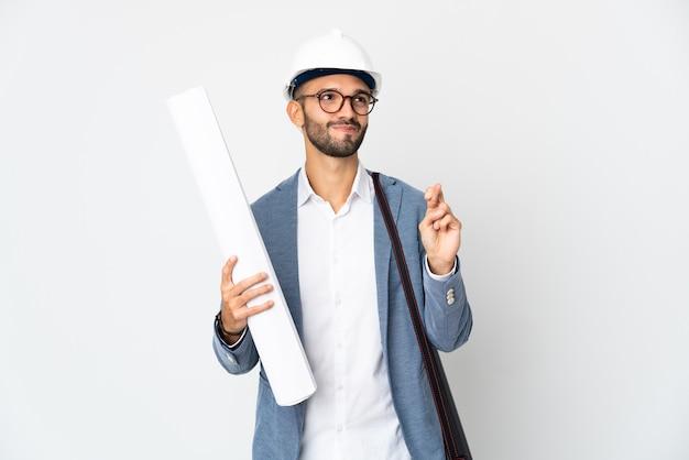 Jeune architecte homme avec casque et tenant des plans isolés sur fond blanc