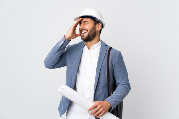 Jeune architecte homme avec casque et tenant des plans isolés sur un mur blanc a réalisé quelque chose et l'intention de la solution