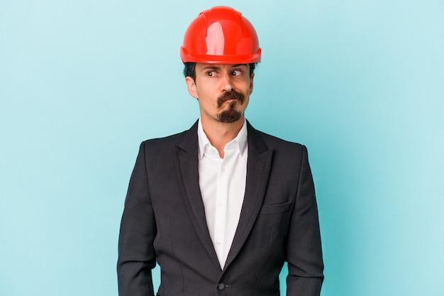 Jeune architecte homme caucasien isolé sur fond bleu confus, se sent dubitatif et incertain.