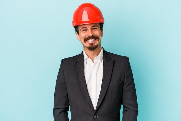 Jeune architecte homme caucasien isolé sur fond bleu heureux, souriant et joyeux.