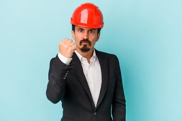 Jeune architecte homme caucasien isolé sur fond bleu montrant le poing à la caméra, expression faciale agressive.