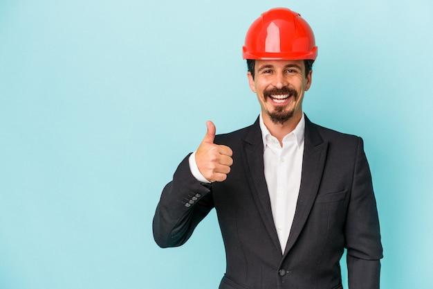 Jeune architecte homme caucasien isolé sur fond bleu souriant et levant le pouce vers le haut