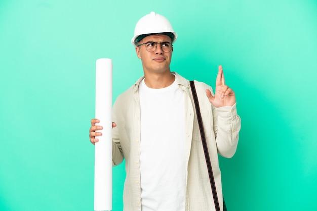 Jeune architecte homme tenant des plans sur fond isolé avec les doigts croisés et souhaitant le meilleur
