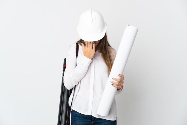 Jeune architecte lituanien femme avec casque et tenant des plans isolés sur un mur blanc avec une expression fatiguée et malade