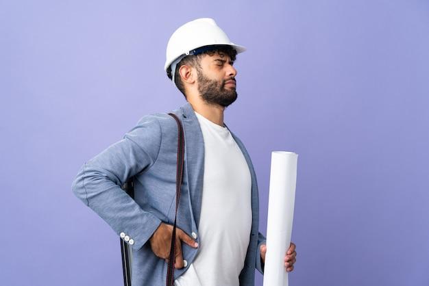 Jeune architecte marocain homme avec casque et tenant des plans sur fond isolé souffrant de maux de dos pour avoir fait un effort
