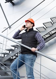 Jeune architecte parlant au téléphone lors de l'inspection de l'usine