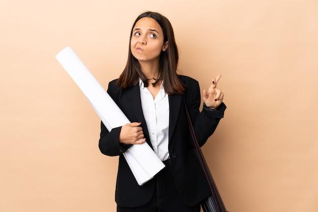 Jeune architecte woman holding blueprints sur fond isolé avec les doigts qui se croisent et souhaitant le meilleur