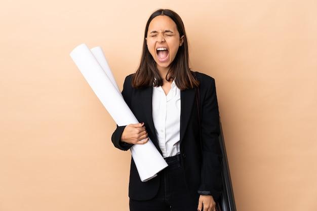 Jeune architecte woman holding blueprints sur mur isolé criant à l'avant avec la bouche grande ouverte
