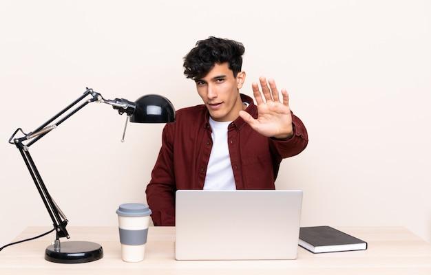 Jeune argentin assis à une table avec un ordinateur portable sur son lieu de travail, faisant un geste d'arrêt avec sa main