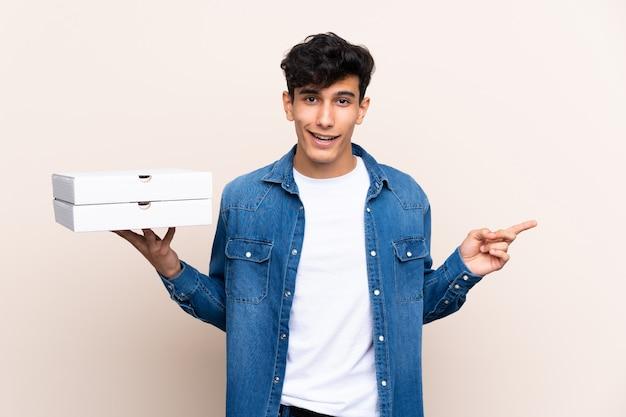 Jeune, argentin, tenue, pizzas, isolé, mur, surpris, pointage, doigt, côté