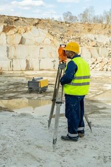 Jeune arpenteur en vêtements de travail à l'aide d'une station géodésique sur un lieu de construction