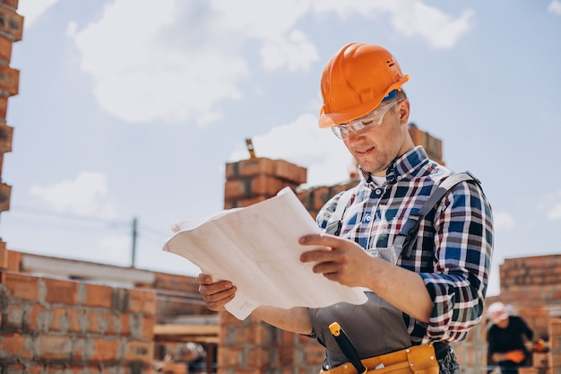 Jeune artisan construisant une maison