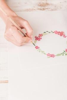 Jeune artiste dessin motif de fleurs avec aquarelle et pinceau sur papier au lieu de travail